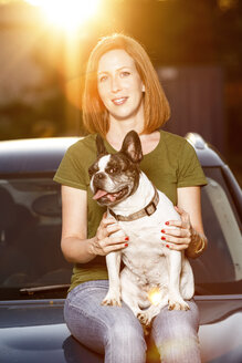 Portrait of redheaded woman sitting on car bonnet with her French bulldog - TAM000310