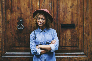 Spain, Barcelona, portrait of smiling young woman wearing hat and denim shirt standing in front of wooden door - EBSF000913