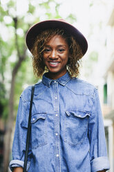 Portrait of smiling young woman wearing hat and denim shirt - EBSF000932