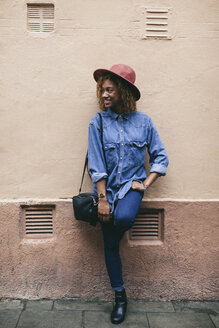 Portrait of smiling young woman wearing hat and denim shirt standing in front of house facade - EBSF000920