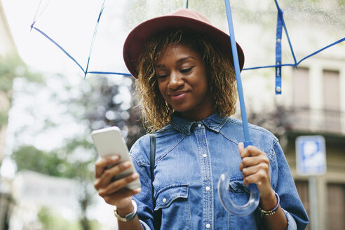 Spain, Barcelona, portrait of smiling young woman with umbrella and smartphone - EBSF000923