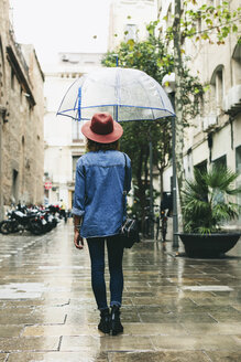 Spain, Barcelona, young woman with umbrella wearing hat and denim shirt - EBSF000926