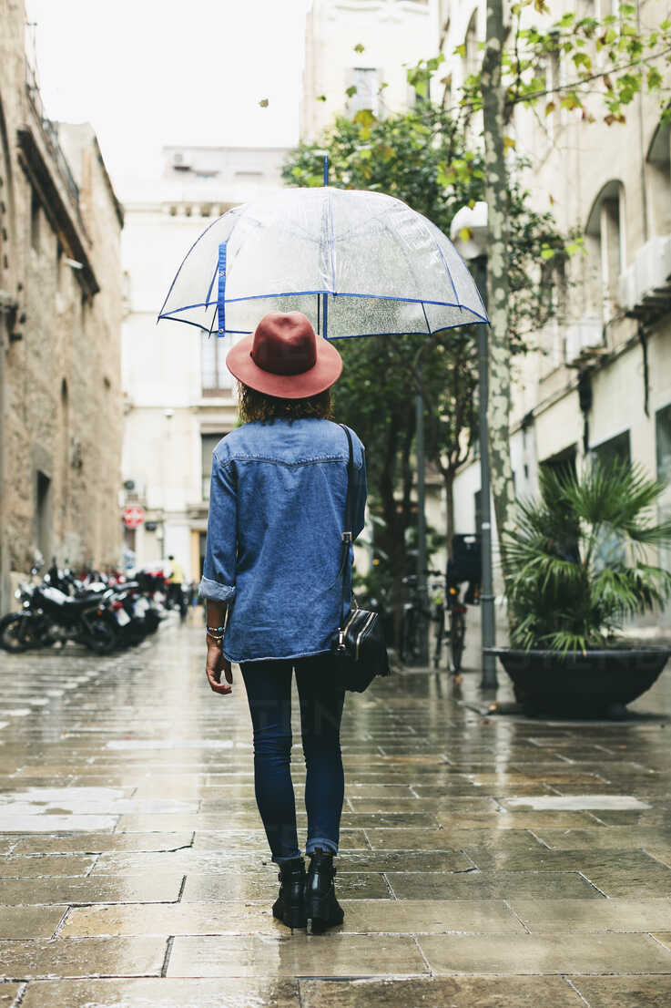Spain, Barcelona, young woman with umbrella wearing hat and denim shirt - EBSF000926 - Bonninstudio/Westend61