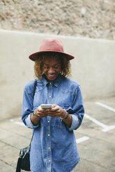 Portrait of smiling young woman wearing hat and denim shirt looking at smartphone - EBSF000928
