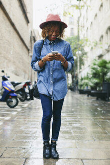 Spain, Barcelona, portrait of young woman wearing hat and denim shirt looking at her smartphone - EBSF000930