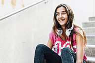 Portrait of smiling teenage girl with headphones sitting on stairs - GEMF000384