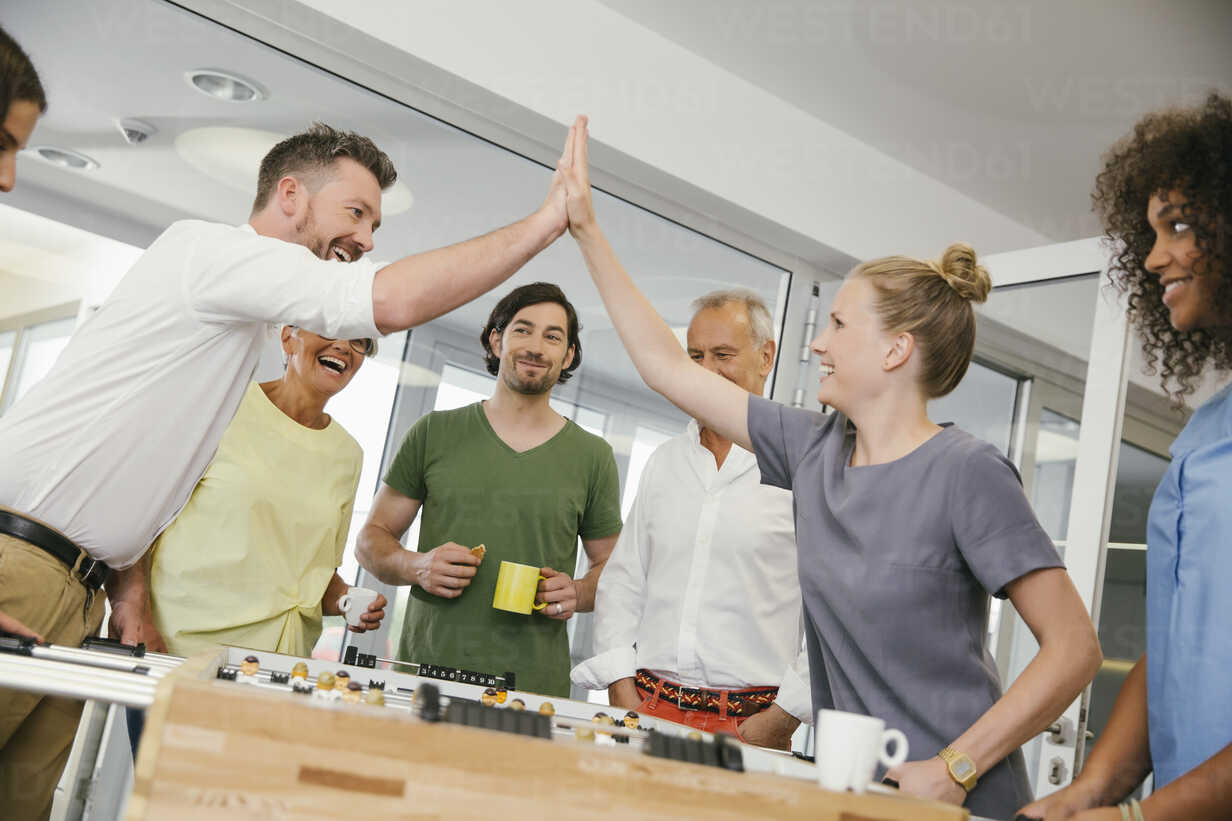 Office colleagues playing foosball during break - MFF002212 - Mareen Fischinger/Westend61