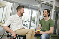 Man in wheelchair talking to colleague - MFF002228