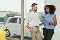 Man and woman talking while charging electric car, woman holding key - MFF002216