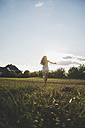 Back view of woman running barefoot on a meadow at backlight - UUF005642