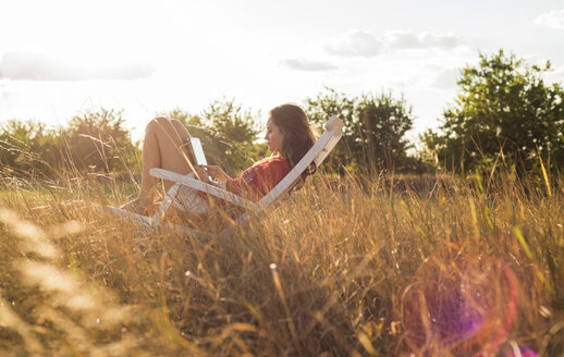 Woman sitting on a deck chair on a meadow using digital tablet - UUF005646