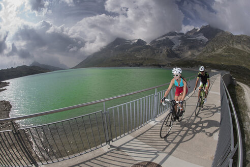 Switzerland, Engadin, two cyclists on a footbridge - FF001459