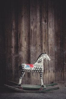 Vintage rocking horse in a barn in front of a wooden wall - IPF000246