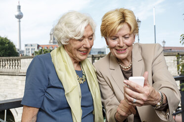 Germany, Berlin, portrait of two smiling senior businesswomen looking at smartphone - TAMF000344