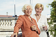Germany, Berlin, portrait of two smiling senior women with glasses of mineral water - TAMF000330