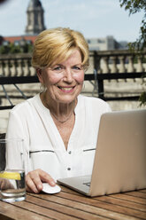 Germany, Berlin, portrait of smiling senior woman with laptop - TAMF000331