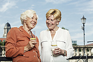 Germany, Berlin, portrait of two smiling senior women with glasses of mineral water - TAMF000333
