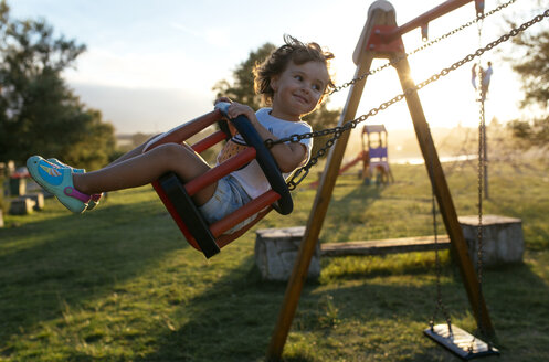 Portrait of happy little girl on a swing at backlight - MGOF000751