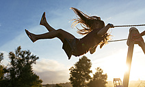 Girl with blowing hair on a swing at backlight - MGOF000752