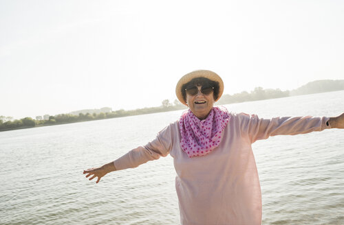 Portrait of smiling senior woman with outstretched arms in front of a river - UUF005706