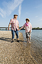 Germany, Ludwigshafen, happy senior couple walking hand in hand at riverside - UUF005667