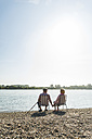 Germany, Ludwigshafen, back view of senior couple sitting hand in hand on folding chairs at riverside - UUF005677
