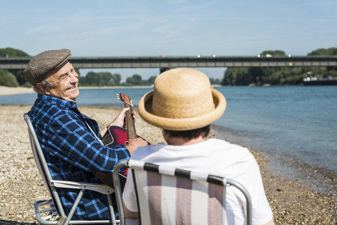 Germany, Ludwigshafen, senior couple with guitar at riverside - UUF005698