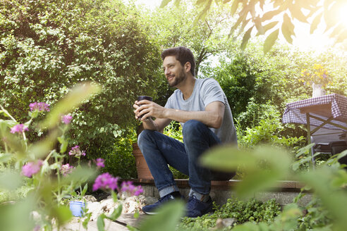 Smiling man sitting in garden with cup of coffee - RBF003203