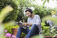 Relaxed man sitting in garden with headphones and magazine - RBF003205