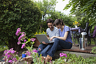 Happy couple sitting on garden terrace using laptop - RBF003165
