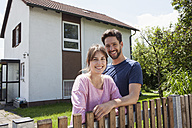Portrait of smiling couple in garden in front of residential house - RBF003179