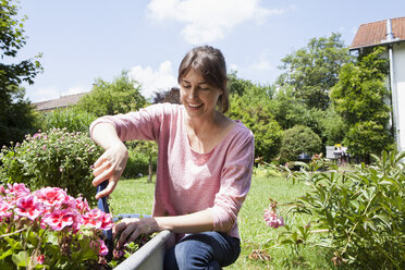 Smiling woman in garden planting flowers - RBF003182