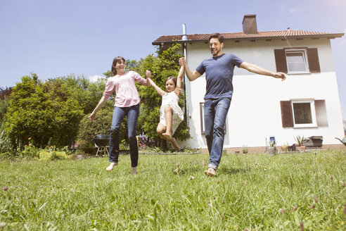 Playful couple with daughter in garden - RBF003223