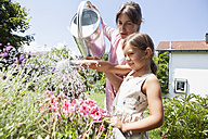 Mother and daughter in garden watering flowers - RBF003227