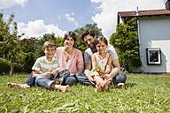 Portrait of smiling family of four in garden - RBF003241