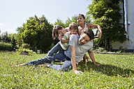 Playful family of four in garden - RBF003243