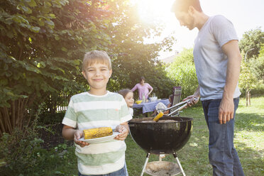 Smiling boy with corn cob on a family barbecue in garden - RBF003249