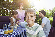 Smiling boy on a family barbecue in garden - RBF003252