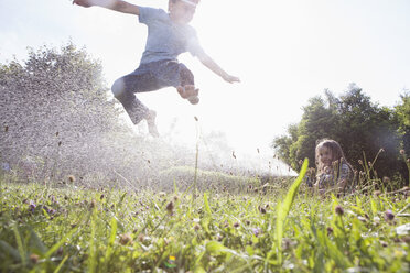 Boy and girl splashing with water in garden - RBF003258