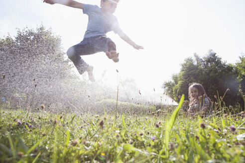 Boy and girl splashing with water in garden - RBF003258