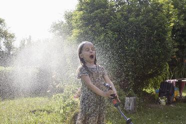 Girl splashing with water in garden - RBF003261