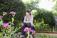Smiling woman sitting in garden relaxing - RBF003192