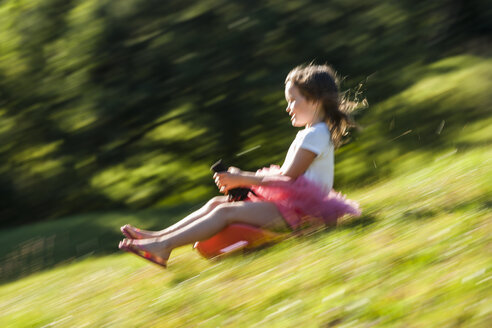 Little girl driving bobsleigh downhill on a meadow - TCF004899