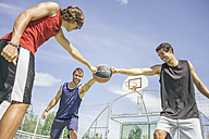 Three young men playing basketball - ABZF000122