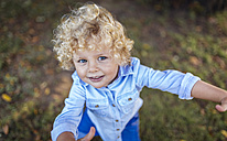 Portrait of smiling blond little boy looking up to camera - MGOF000765