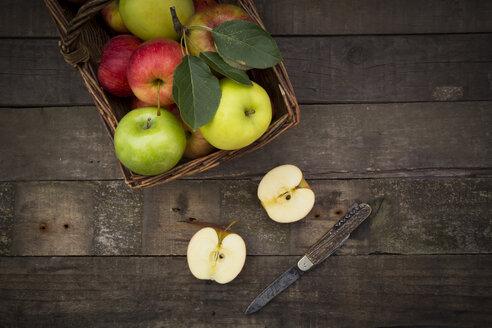 Different apples, basket and pocket knife on wood - LVF003843