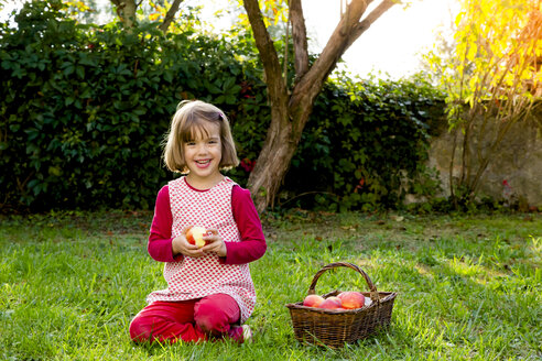 Portrait of smiling little girl sitting on a meadow with wickerbasket of apples - LVF003868