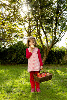 Portrait of little girl standing on a meadow eating an apple - LVF003871