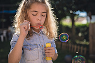 Little girl blowing soap bubbles - RAEF000500
