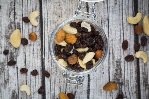 Mixed nuts and raisins in glass on wood - LVF003879